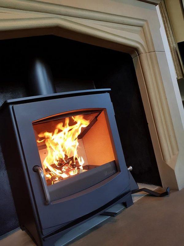 Dik Geurts Ivar 5 Lit Wood Burning Stove in a stone fireplace