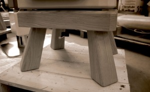 A close up shot of the wooden legs on a stack stove