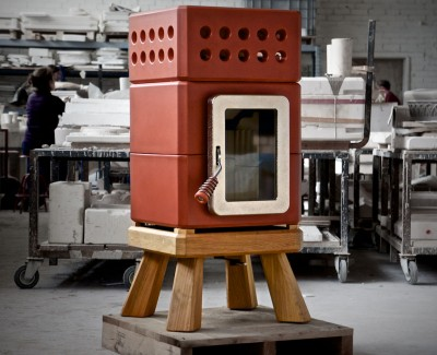 Red designer wood burning stove on a wooden base, sat on a pallet in a factory in Italy
