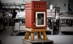 A Red mini stack stove with wooden feet in the factory being finished