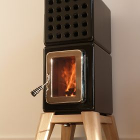 ceramic black stack stove on wooden legs, the stove has been lit and the fire is burning inside the stack stove, manufactured by La Castellamonte, installed by Hot Box Stoves
